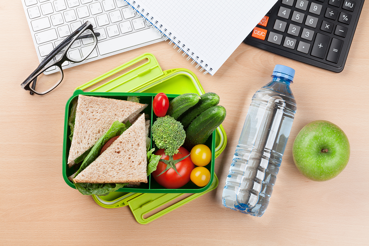 a lunchbox surrounded by office desk equipment - self-care strategies for primary school teachers