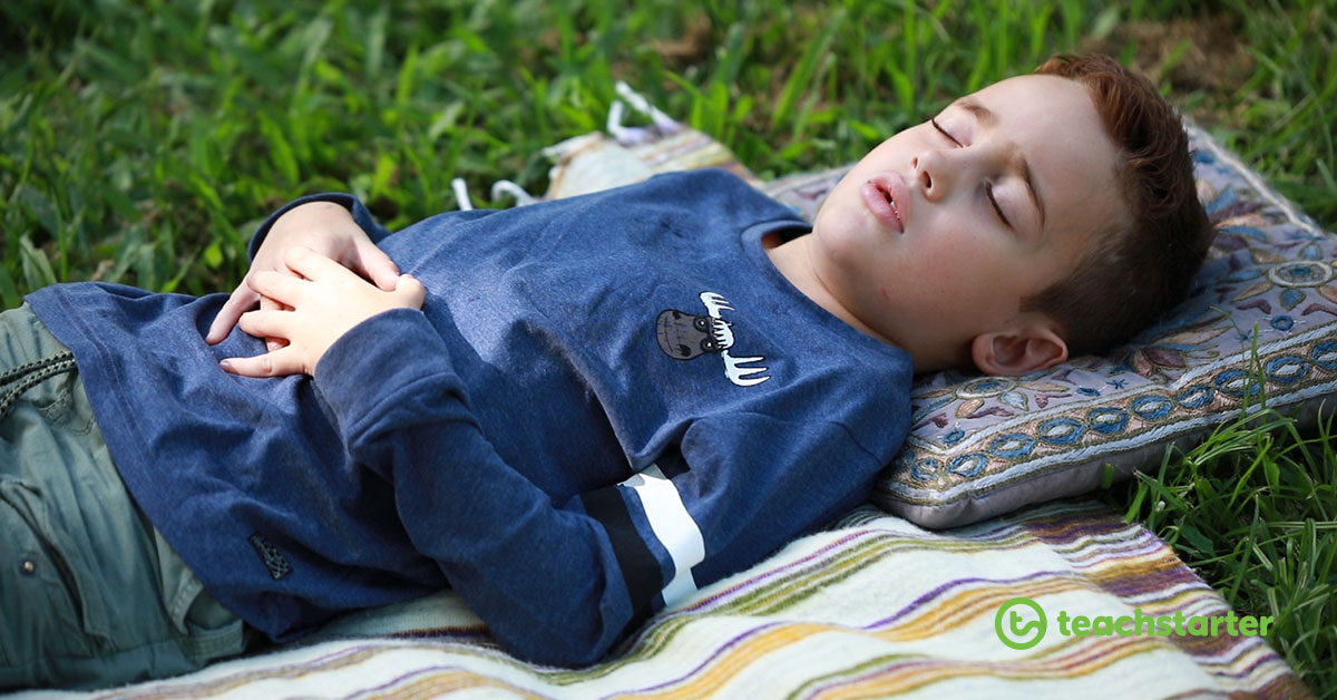 Boy laying on a blanket outside, with his eyes closed and hands on his belly