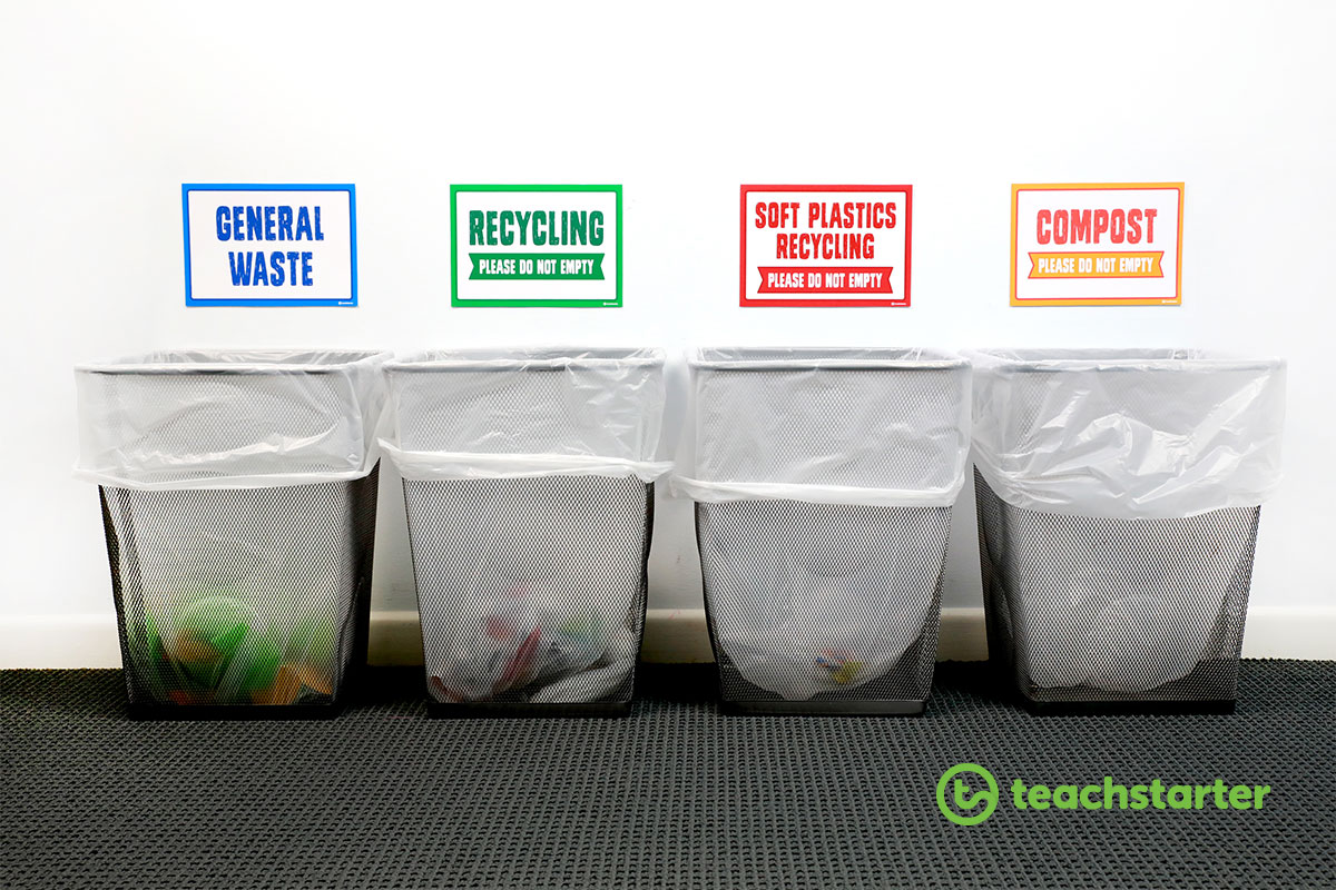 a row of four bins with signs above - general waste, recycling, soft plastics recycling and compost