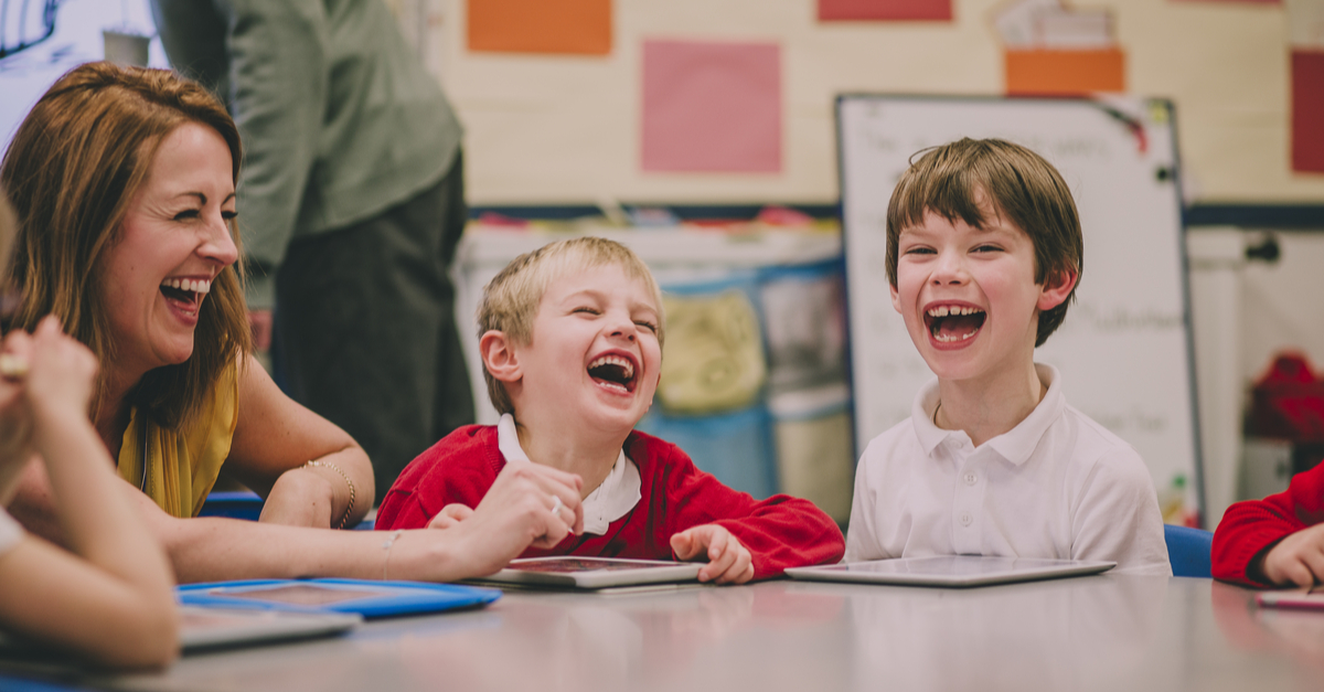 kids laughing with their teacher in the classroom
