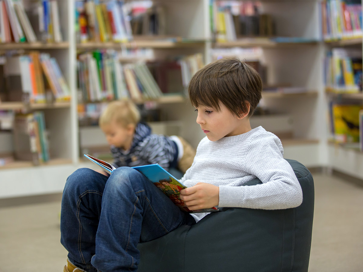Library Activities for Kids - Boy reading in the library
